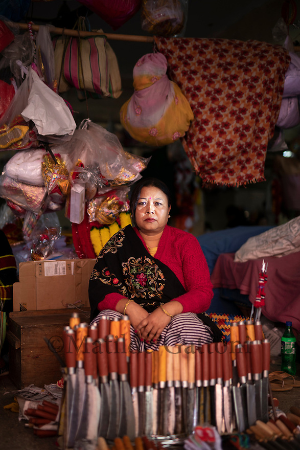 India - Manipur - Imphal - Leishangthem Kananbala, 44 years old. From Wangkhei Imphal East.She has been working in the Ima Market for nine years. The stall belongs to one of her aunts, it's a clan thing, her aunt couldn't continue, so she bought the stall permanently from that aunt,She belongs to the clan of the knives from her father side. Only this clan can make the knives, and only the clan can sell knives, only for the Ima Market - it doesn't apply in other parts of Manipur (the clan name is Thangjam). Other clans produce knives, but only the Thangjam clan is allowed to sell them in the Ima Market.