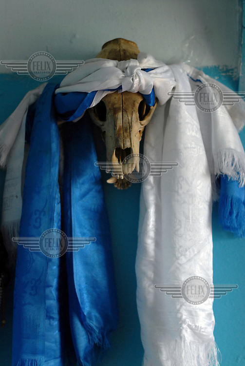 A decorated animal skull, used by those who practise Shamanism. Shamans, religious figures called upon to explain and solve misfortunes that strike their community, have existed in this region for centuries. According to the shamanic worldview, the world is divided into a real world and an invisible one, the latter being a projection of the real world inhabited by spirits whose actions influence the life of humans. Shamans are believed to have the power to see the invisible world and communicate with spirits.