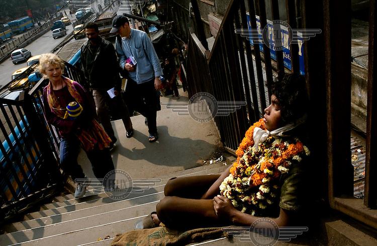 Tourists walk past a begger sitting on a pedestrian footbridge in Kolkata....