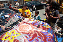 August 15, 2009. Nine year old Aiko Kennedy from Oakland paints the earth on an 'art car.' About two hundred people participated in a rally, march, and demonstration protesting Chevron's Richmond oil refinery renovation and expansion project. The event was organized by Mobilization for Climate Justice-West, a coalition of over thirty organizations, working to bring awareness to the refinery issue as well as the United Nations Climate Change Conference taking place in December in Copenhagen. Event organizers claim that the Richmond refinery project will allow the facility to refine heavier and dirtier crude that will result in more air pollution, greenhouse gas (GHGs) emissions, and health risks. A court ruling recently put the refinery project on hold saying that further environmental impact reporting was needed. Many protesters were also concerned about the environmental and human health impacts of oil company projects outside the United States. Richmond, California, USA