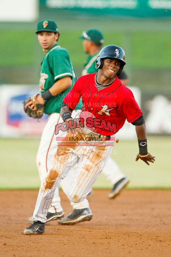 Tim Anderson (2) of the Kannapolis Intimidators hustles towards third base as Greensboro Grasshoppers shortstop Anthony Gomez (2) looks on at CMC-Northeast Stadium on July 15, 2013 in Kannapolis, North Carolina.  The Intimidators defeated the Grasshoppers 4-0.   (Brian Westerholt/Four Seam Images)