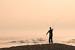 Fisherman casting from beach into Mediterranean Sea at dusk, Costa del Sol, Spain