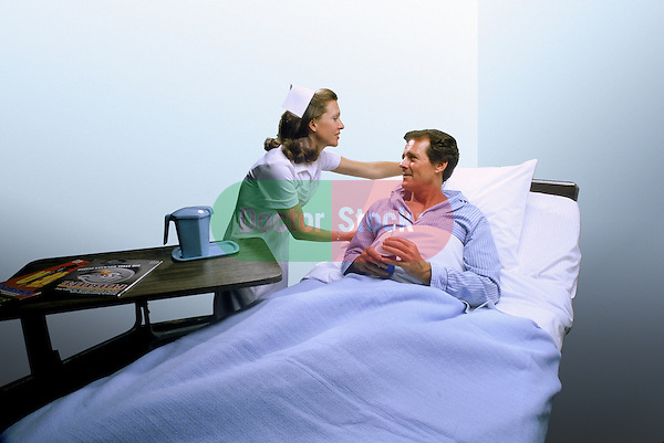 nurse attending to, propping pillow of male patient in hospital bed