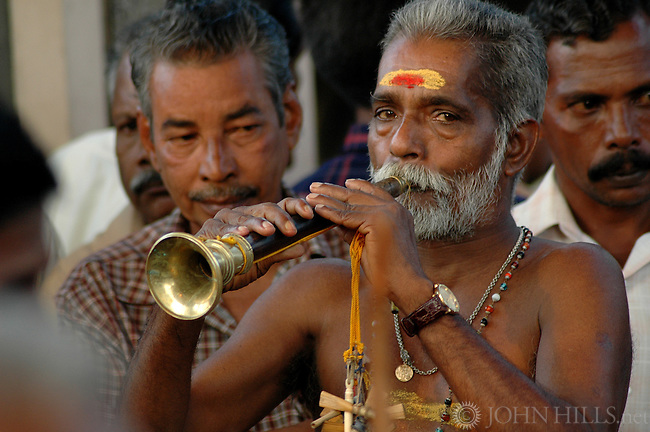 Kochi, Kerala, South India - A musician plays a raga on the shennai at a Shiva festival to the accompaniment of drums and cymbals. The shennai is an  quadruple-reed Indian wind instrument. For centuries the shennai has held an important position in Indian culture.