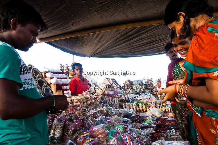 Young women gather to buy bangles from a makeshift shop on Puri Beach along the Bay of Bengal in Puri, Orissa, India. A dip in its salty waters is believed to hold great religious significance, as a result these golden sand beaches sees is a never-ending rush of pilgrims and tourists. Photo: Sanjit Das/Panos
