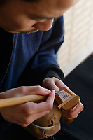 Shogi playing piece carver Gekkou at work, Nakajima Seikichi Shoten, Tendo, Yamagata Prefecture, Japan, February 19, 2018. The city of Tendo in Yamagata Prefecture is famous for its shogi (Japanese chess) playing pieces. Production started early in the 19th century and Tendo still produces over 95% of the Shogi pieces made in Japan.