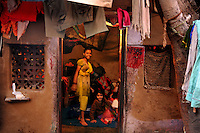 Two girls at their house at Katputly colony in New Delhi, India. 17.11.2009. Kathputly colony is a slum area in West Delhi. This slum seems like any other slum areas of modern India with dysfunctional electricity, non existing sanitation and poverty. As a part of Delhi, this is also ailed with water crisis. Large families live their lives crammed together in a single room with all the odds which complement poverty. One thing which differentiates this slum with any other is the people living in the colony. Nearly everybody in this slum is a traditional performing artist; and they have been migrating to this area for last 50 years from different parts of the country for a better livelihood. They are magicians, acrobats, jugglers, puppeteers, dancers and musicians. These artistes perform in star rated hotels, marriage ceremonies of the richer section, functions, and festivities all around the country and the world. Most of the artisans I met here, have performed in Europe and America but such opportunities are rare to come by. They struggle to keep their art form alive. They say that they don't get any help or support from the government for their basic needs and for the well being of the Kathputly colony -  though they have uphold the prestige of the country internationally. Polluted air, dirty alleys smelling of urine, colourful dress and sound of music characterise Kathputly colony, which is the one of its kind in India. Arindam Mukherjee