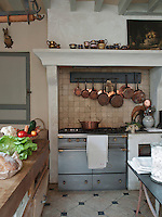 A traditional kitchen with a tiled floor. A set pf copper saucepans hang above a range oven, which is set in a tiled recess.