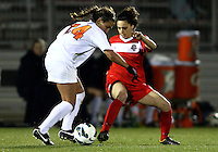 BOYDS, MARYLAND - April 06, 2013:  Domenica Hodak (4) of The Washington Spirit goes in to tackle Danielle Colaprico (24) of the University of Virginia women's soccer team in a NWSL (National Women's Soccer League) pre season exhibition game at Maryland Soccerplex in Boyds, Maryland on April 06. Virginia won 6-3.