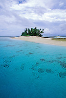 The calm, clear blue Pacific ocean surrounds the white sand crescent of Mili Atoll in the Marshall Islands