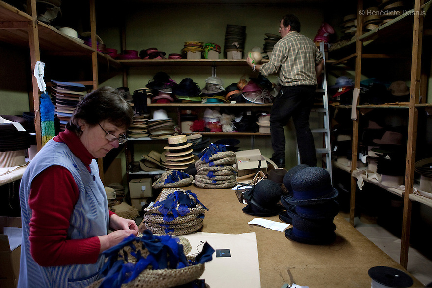 9 december 2009 - Coustilleres' hat factory, Septfonds, France - Marie France Escaffre works at the Coustilleres' hat factory since 20 years. She prepares the Lanvin Haute couture's hats to be send. On the back, Jean Claude Coustilleres working..Septfonds is the heart of French straw hat making, due to its very ancient hatter tradition. The hat making industry had its commercial peak in the late 19th century..Coustillères is a family owned hat making factory that has been making straw hats in Septfonds for nearly 100 years. They make hats from straw, felt, and cloth as well as caps. The current owner is Jean-Claude Coustilleres. He is one of the last hat makers of the region..The straw hat making process is very labor intensive and numerous hands are involved. Nearly all of the equipment is over 100 years old, they use the original presses and tools including aluminium molds and sewing machines and dye their own straw continuing the traditional methods of manufacturing. The hat blocking and shaping, straw braids construction and dyeing are all done by hand..The company works on behalf of fashion houses and makes a variety of regional and historical hats. It produces 2 collections a year distributed by a network of salespeople and through a catalog to clients around the world. Photo credit: Benedicte Desrus