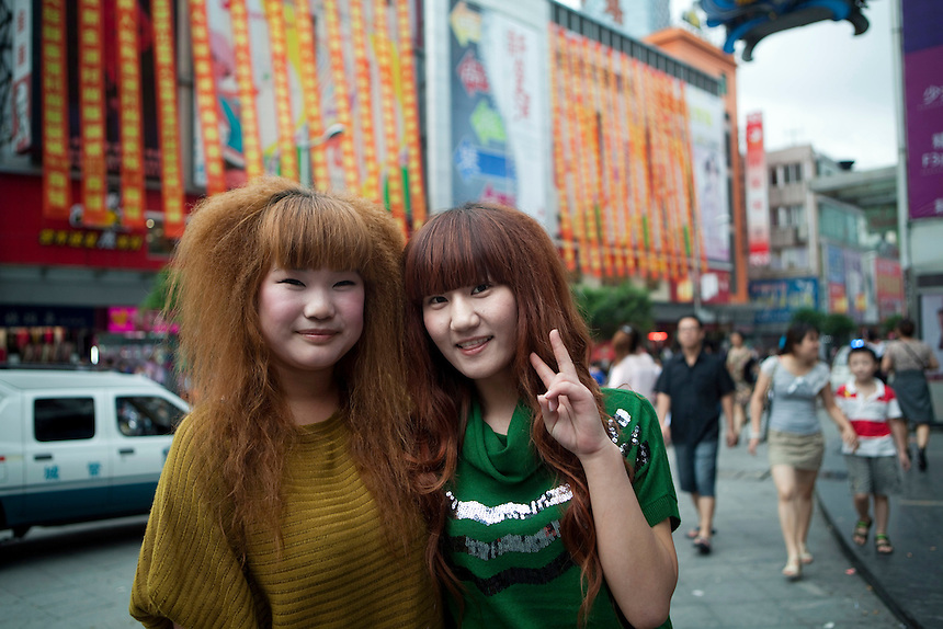Two women with modern hair styles at a textile market in Shanghai.