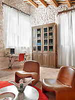 The sitting room/come study is richly textured from the rough brickwork and rustic terracotta tiles to the aged leather of the armchairs and smooth marble of the coffee table