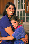 portrait of mother embracing girl in kitchen