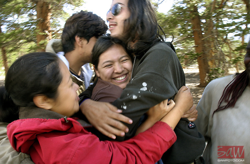 "EcoAcademy High School Case Manager Nancy Maldonado,center, receives an enthusiastic squeeze from Outward Bound Adventures participants after arriving at the parking lot to bring the teens home to LA, student Christian Barahona.center. Profile of Outward Bound Adventures, a nonprofit organization that introduces at-risk urban teens to the therapeutic benefits of time spent in the wilds, there motto is; ""Share the Earth, Challenge a Child""."