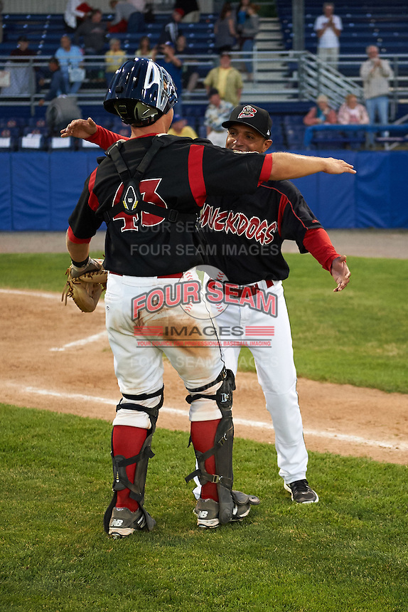 Batavia Muckdogs catcher Korey Dunbar (43) hugs manager Angel Espada (4) after a game against the Mahoning Valley Scrappers on June 24, 2015 at Dwyer Stadium in Batavia, New York.  Batavia defeated Mahoning Valley 1-0 as three Muckdogs pitchers combined to throw a perfect game.  (Mike Janes/Four Seam Images)
