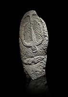 Late European Neolithic prehistoric Menhir standing stone with carvings on its face side. The representation of a stylalised male figure starts at the top with a long nose from which 2 eyebrows arch around the top of the stone. below this is a carving of a falling figure with head at the bottom and 2 curved arms encircling a body above. at the bottom is a carving of a dagger running horizontally across the menhir.  Excavated from Barrili II site,  Laconi. Menhir Museum, Museo della Statuaria Prehistorica in Sardegna, Museum of Prehoistoric Sardinian Statues, Palazzo Aymerich, Laconi, Sardinia, Italy. Black background.