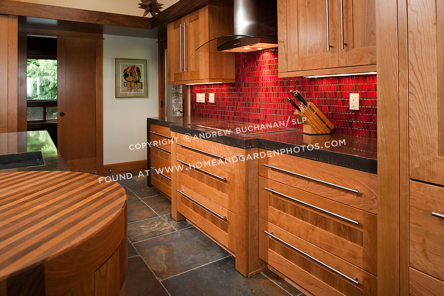 Custom cherry cabinetry, bright red tile, and a slate tile floor complement one another in this striking kitchen.