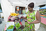 Evanis Gatunzi, a refugee from Rwanda, picks out eggplants in the Durham Farmers' Market in Durham, North Carolina. Gatunzi was assisted on her arrival in Durham by Church World Service, which resettles refugees in North Carolina and throughout the United States.<br /> <br /> Photo by Paul Jeffrey for Church World Service.