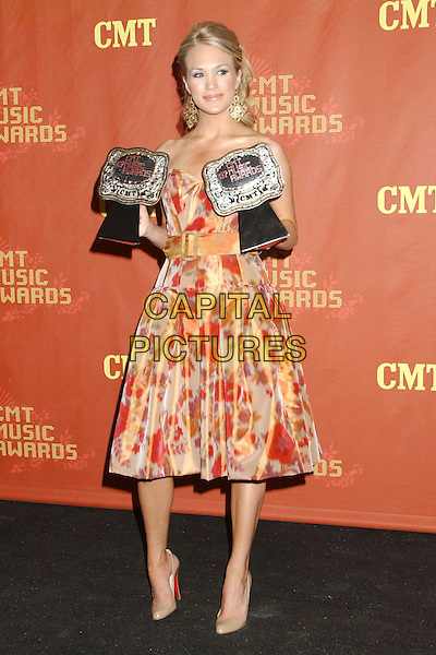 CARRIE UNDERWOOD.2007 CMT Music Awards held at Curb Event Center, Nashville, Tennessee, USA..April 16th, 2007.country music pressroom full length awards trophies red orange patterned strapless dress.CAP/ADM/LF.©Laura Farr/AdMedia/Capital Pictures
