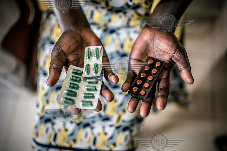 A client with a urinary tract infection displays her medications at the RHU (Reproductive Health Uganda) clinic.