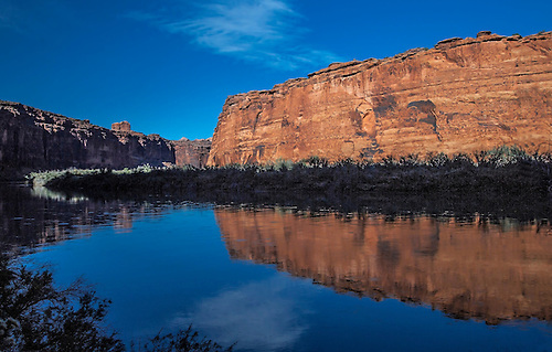 The sandstone banks near Moab, Utah are reflected in the still Colorado River