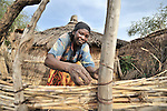A woman who fled violence in Darfur builds a wall around her hut in the Goz Amer refugee camp in eastern Chad. More than a quarter million residents of Darfur live in camps in Chad, along with almost 200,000 Chadians who have been internally displaced by related violence.