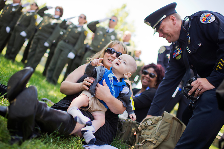 UNITED STATES - MAY 15: William Parks, 6 months, sits with his godmother Devin Somerville and godfather Officer John Somerville of the Chandler (Ariz.) Police Department, during the 34rd Annual National Peace Officers' Memorial Service on the West Lawn of the Capitol, May 15, 2015, which was part of National Police Week. William's father is Officer David Park of the Chandler PD. (Photo By Tom Williams/CQ Roll Call)