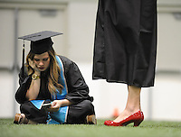 NWA Media/ANDY SHUPE - Hannah Sellers of Bryant looks at her cellphone while waiting with other graduates before the start of the University of Arkansas fall commencement exercises Saturday, Dec. 20, 2014, at Barnhill Arena on the university campus in Fayetteville.