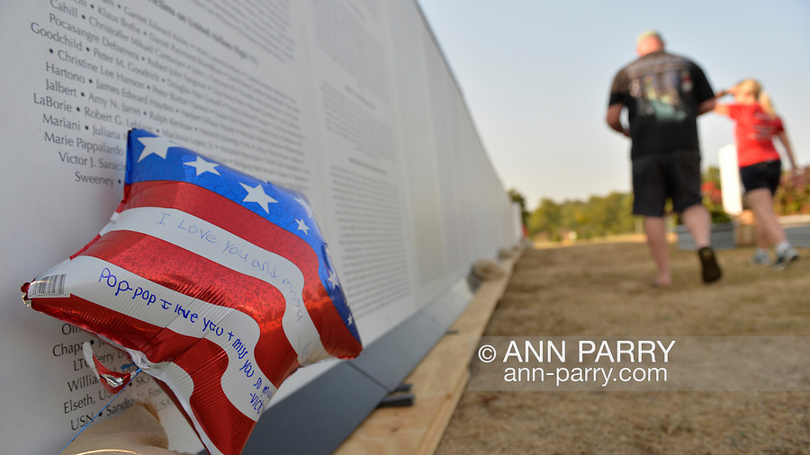 """East Meadow, New York, U.S. 11th September 2013. A patriotic red white and blue balloon has messages written on it to William V. Steckman (Pop-Pop) of West Hempstead, who worked for NBC in the North Tower of Twin Towers, and died 9/11 2001. A man and woman are walking along the Global War on Terror """"Wall of Remembrance"""" a traveling memorial on display in New York for the first time, is at Eisenhower Park on the 12th Anniversary of the terrorist attacks of 9/11. The unique 94 feet long by 6 feet high wall has, on one side, almost 11,000 names of those lost on September 11, 2001, along with heroes and veterans who lost their lives defending freedom of Americans over past 30 years. On the wall's other side is a timeline, with photos, covering 1983 to present day."""