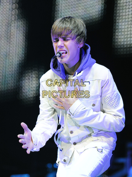 "JUSTIN BIEBER.performs live during his ""My World Tour""  at Honda Center in Anaheim, California, USA, October 27th 2010..concert gig on stage music half length white jacket purple hoodie jeans microphone headset singing hands eyes shut                                                             .CAP/RKE/DVS.©DVS/RockinExposures/Capital Pictures."