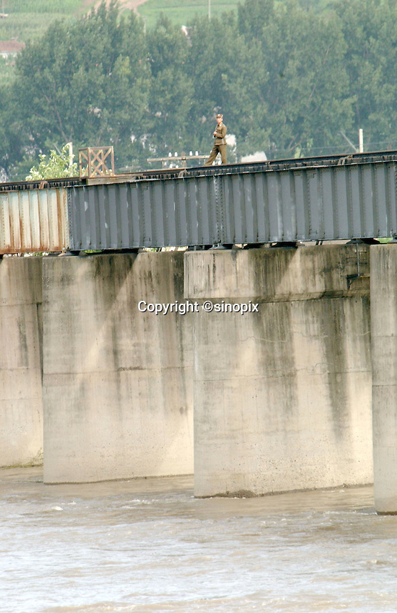 01-AUG-02: NORTH KOREAN BORDER: TUMEN, JILIN, CHINA<br /> An armed North Korean border guard stands on the railway bridge linking China and North Korea at the Chinese - North Korean border town of Tumen. The heavily policed border is often breached by refugees escaping hunger and famine from North Korea.