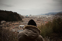 A man looks out over the devastated town of Rikuzentakata. Thousands of people died in this small town which ran out of body bags. On 11 March 2011 a magnitude 9 earthquake struck 130 km off the coast of Northern Japan causing a massive Tsunami that swept across the coast of Northern Honshu. The earthquake and tsunami caused extensive damage and loss of life.