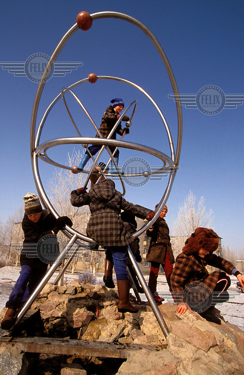 © Paul Lowe / Panos Pictures..Semipalatinsk, KAZAKHSTAN. ..Children of workers in Kurchatov play on a giant sculpture of an atom in the centre of the city.  The town is named after the Father of the Russian atomic bomb programme.  Until 1974 it was just called Semipalatinsk 21, and is not marked on maps of the region.  ..On 29th August 1949 the first Russian plutonium bomb was exploded at the Semipalatinsk nuclear test site, which came to be known as 'The Polygon'. This first detonation was followed by more than 500 nuclear explosions, both atmospheric and underground..The effects in the Semipalatinsk region have been devastating. According to the UN more than 1.2 million people have been contaminated or are living in severely contaminated areas. Of these over 100,000 suffer from radiation related diseases. Even though testing stopped in 1989 the situation is continuing to deteriorate. Two out of every three children born in the region suffer from genetic defects.