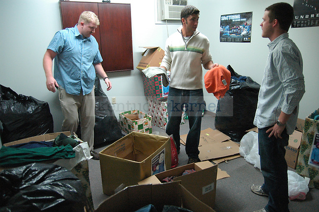 Graduate students Nick Gould and Jacob Sither, talk with psychology junior Dustin Froelich while sorting through the clothes that were donated to the Wildcat Warmth project at the Reynolds building on Thursday, November 12th 2009. Photo by Jon Reynolds | Staff