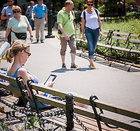 A reader basks in the sun reading her electronic book in Washington Square Park in Greenwich Village in New York on Tuesday, May 21, 2013. . The temperature is expected to hit the high 80's this afternoon with a chance of spotty thunderstorms. (© Richard B. Levine)