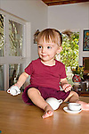 One and a half year old brunette toddler female sits on counter in house holding small cups