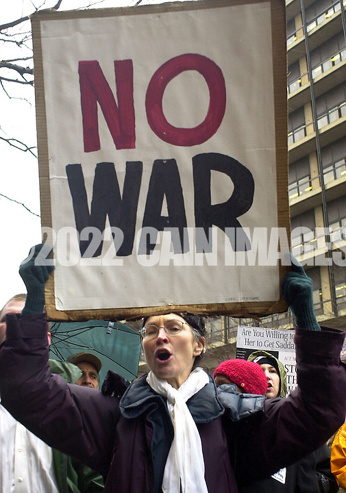 "Protester Lynn Mather, of Philadelphia, Pennsylvania, holds a ""NO WAR"" sign during a protest against war with Iraq, March 20, 2003, in Philadelphia, Pennsylvania. The protestors blocked the entrances to the Federal Courthouse, and demanded that the U.S. pull out of Iraq. 80 protesters were arrested on federal charges. (Photo by William Thomas Cain/photodx.com)"