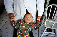 CHINA. Beijing. A young orphan in an orphanage outside of Beijing. 2007. There are currently millions of orphans in China living in orphanages spread throughout the country. As a result of China's one-child policy, many children are abandoned or given up if they suffer from any physical or mental handicap as the parents strive to have a child born 'normal' and well. This has led to may children being abandoned to live in state and privately-owned orphanages.
