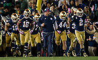 Brian Kelly leads his team onto the field.