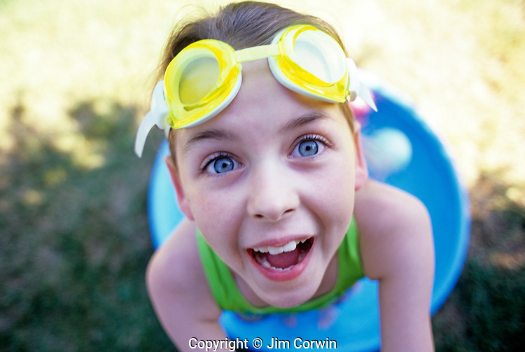 Young girl ( 9 yrs old) with water goggles on head looking right in the camera with a happy clowning around, summer fun, kind of face