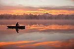 Sunrise in fog Lake Cassidy with fisherman in small fishing boat.