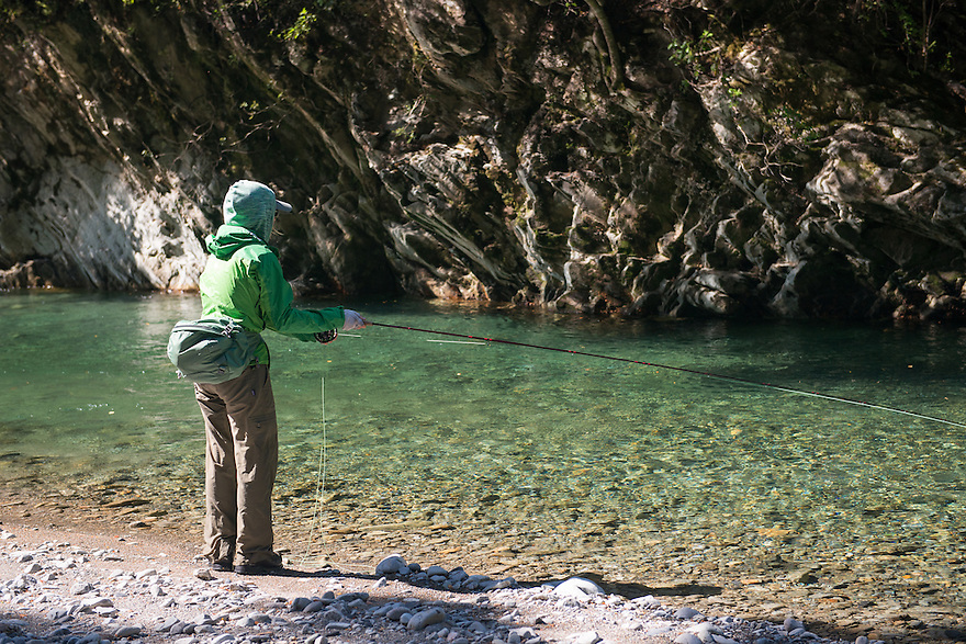 Christine Marozick of Bozeman, Montana fishes for brown trout on a backcountry river in Kahurangi National Park, South Island, New Zealand.