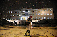 Pictured: A woman walks past the Greek Parliament in Syntagma Square, Athens, Greece. Monday 09 January 2017<br /> Re: Heavy snow fall and minus zero temperatures have affected most parts of eastern Europe and Greece.