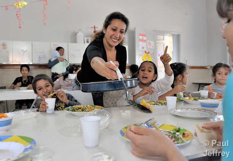 An Iraqi woman, Souad Wahid Aatwaan, dishes up food for her children and others living in a shelter outside Beirut for Iraqi refugees and other residents of Lebanon who have suffered from domestic violence. The shelter, a program of the Caritas Lebanon Migrant Center, which is funded by Catholic Relief Services, the relief and development agency of the U.S. Catholic community, is located in an unnamed community on the outskirts of Beirut.