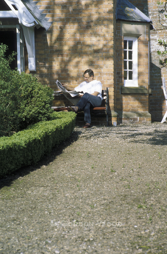 Man Reading Newspaper Outside English Cottaqe on Sunny Morning