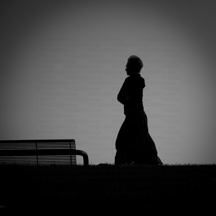 A female walking alone beside a bench in silhouette