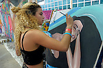 Garden City, New York, USA. September 13, 2015. GRACEE ALBERT, of Wantagh, from Wantagh, paints a painting of a woman, next to a wall of urban art murals by contemporary artists, outdoors at the United Ink Flight 915 Tattoo convention at the Cradle of Aviation Museum in Long Island. The word Paz, peace, is part of the woman's arm tattoo.