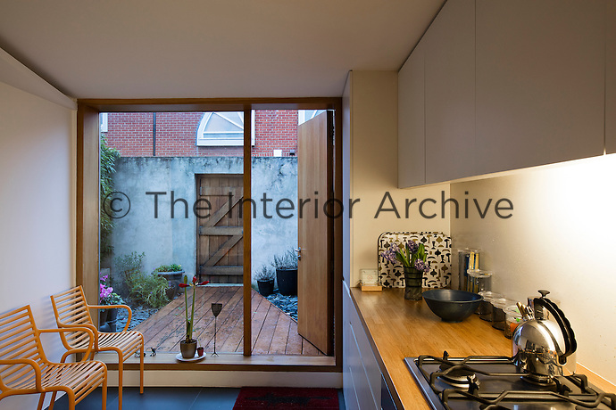 A Victorian home has been given a modernist aesthetic. In the kitchen, the back wall was replaced with a floor-to-ceiling picture window overlooking the small back garden.
