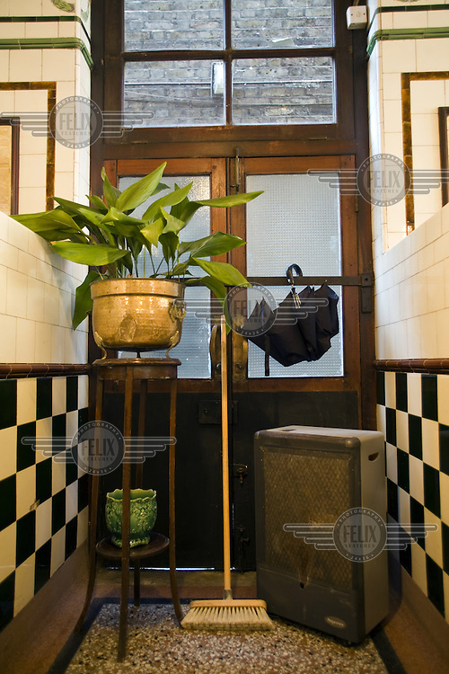 An antique flower pot stand, a broom and an umbrella in Manze's Eel, Pie and Mash shop in Walthamstow, East London. Although the shop still trades under the original Manze name, it is now independently owned and no longer part of the Manze family.